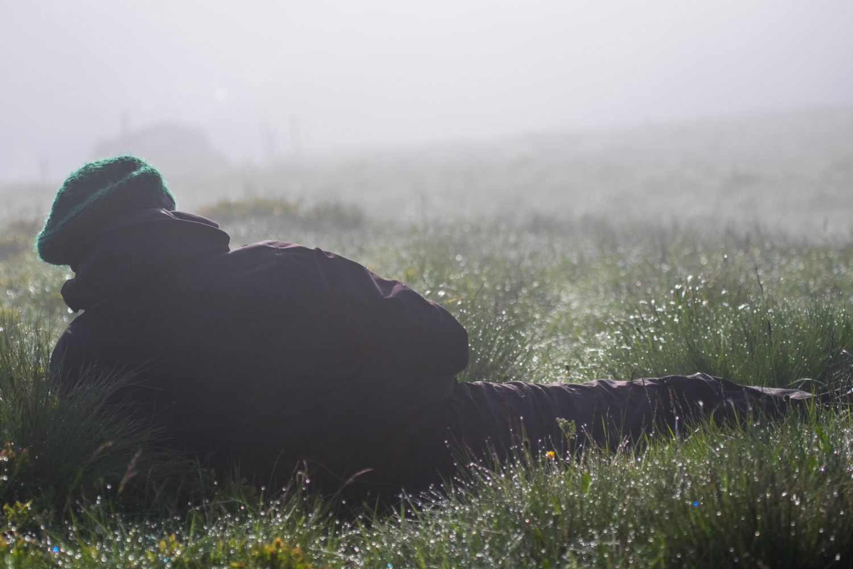 Fotograf liegt im Gras im Morgentau