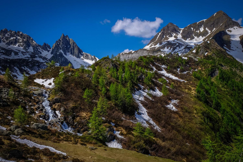 Berghänge mit Restschnee und vereinzelten Bäumen