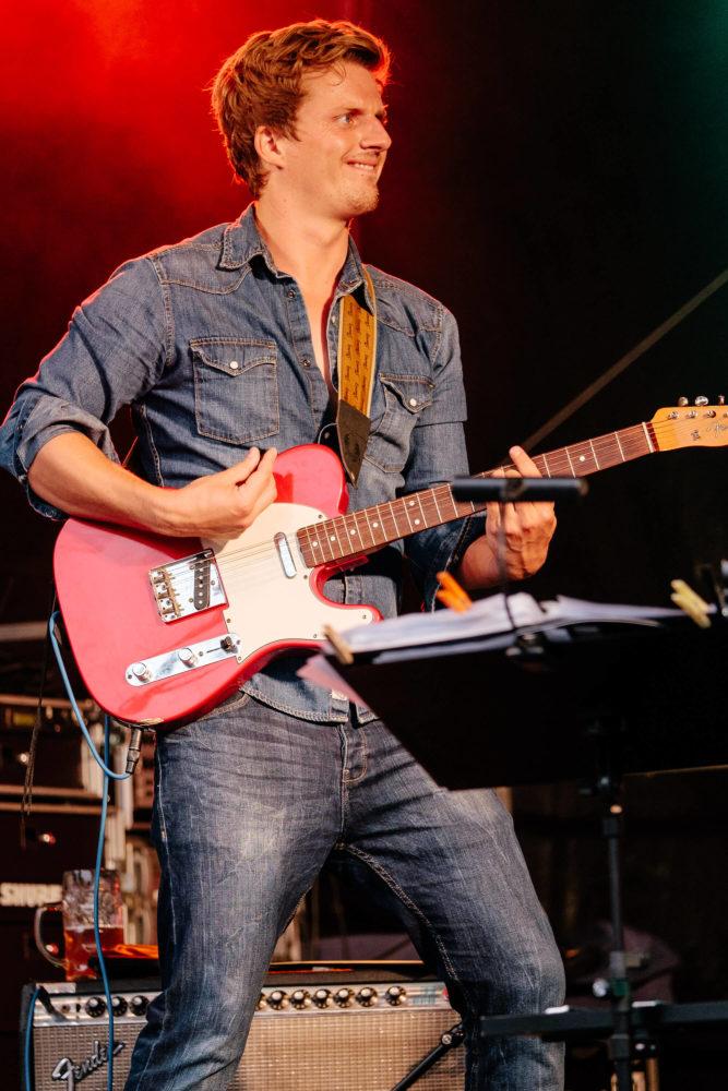 Georg Latz mit Jeansjacke spielt energisch Gitarre