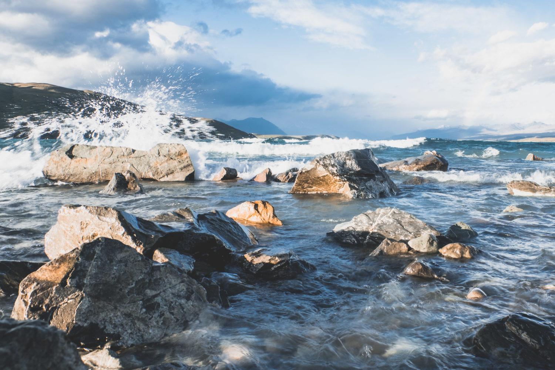 Welle spritzt gegen Steine im Wasser