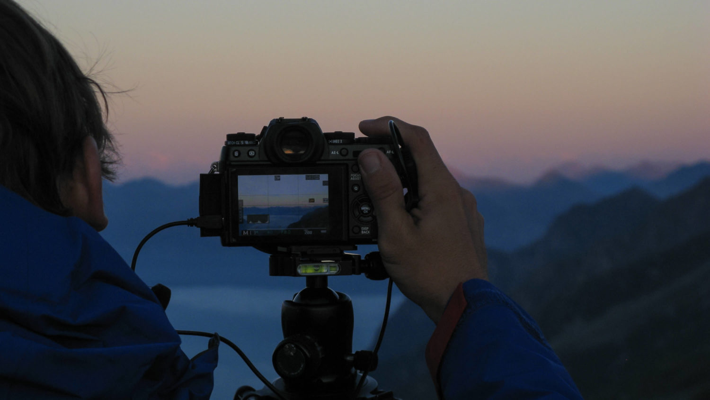 Jan Becker mit Hand an Kamera vor Bergkulisse
