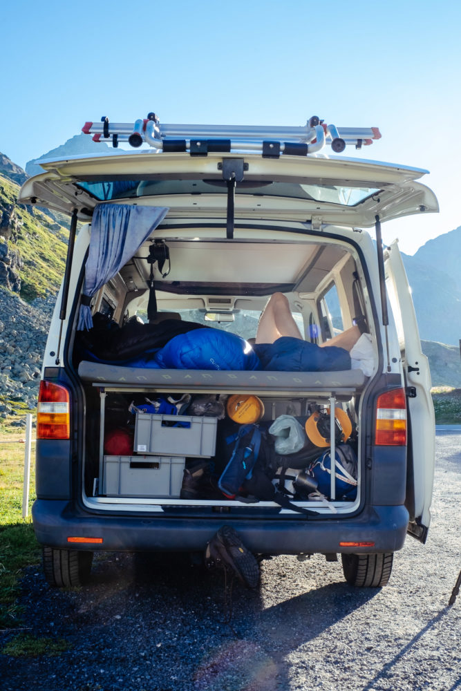 VW Bus mit offener Heckklappe und Wanderausrüstung