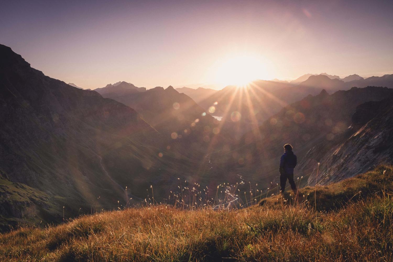Christopher Püschel steht bei Sonnenaufgang am Berghang