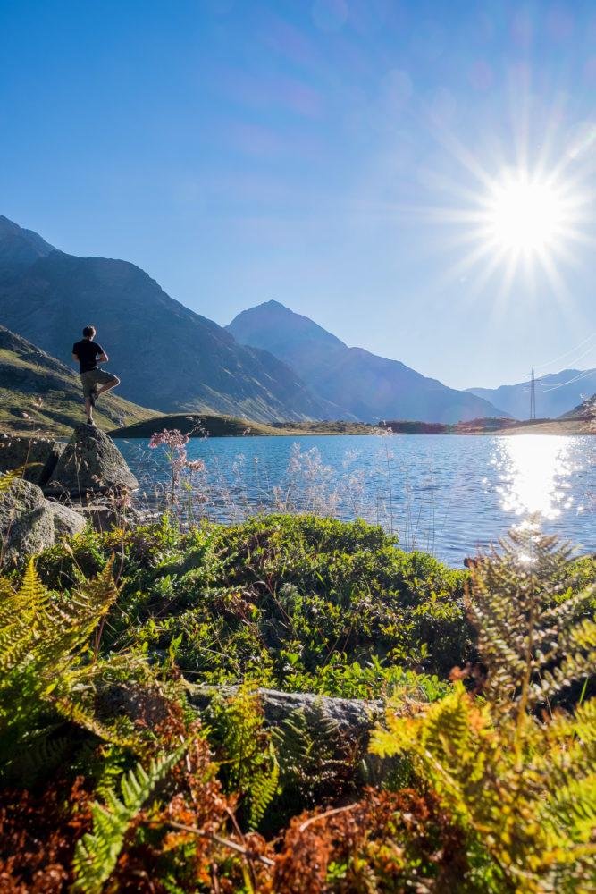 Mensch macht Yogapose am See bei Sonnenschein