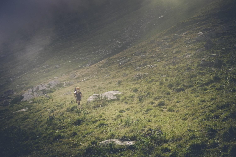 Wanderer durchquert Alpenwiese