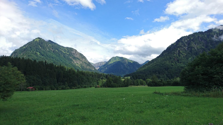 Grüne Wiese und Berghänge bei blauem Himmel