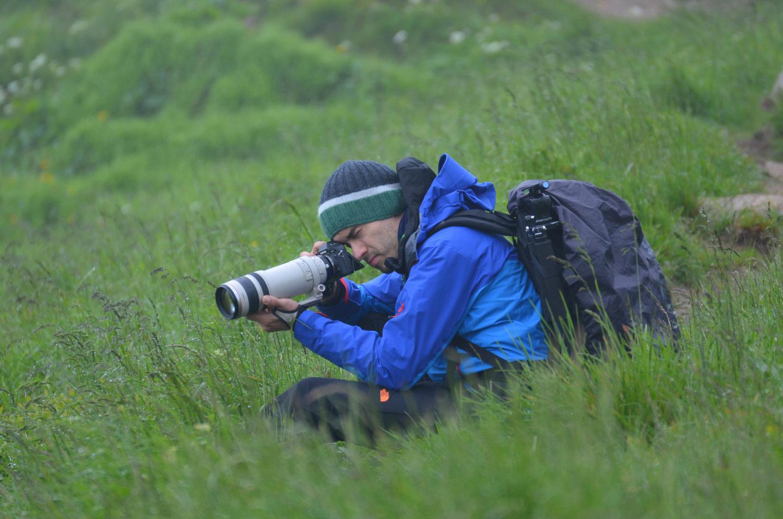 Fotograf kniet mit Fujifilm Kamera, Rucksack und Stativ im Gras