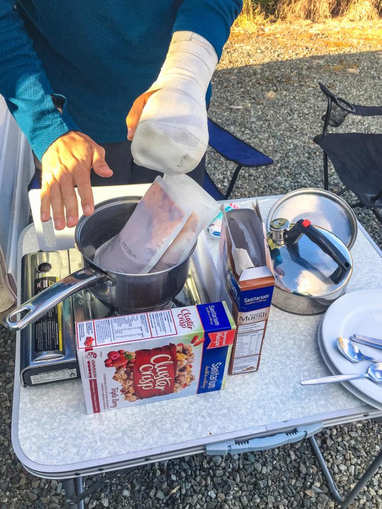Essen wird auf einem Campingkocher mit WIndschutz gekocht