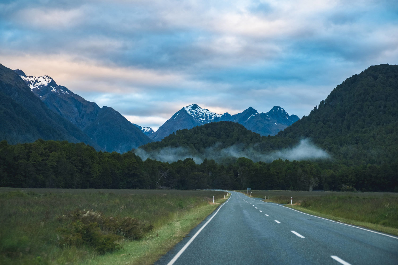Straße mit Wald und schneebedeckten Bergen im Hintergrund