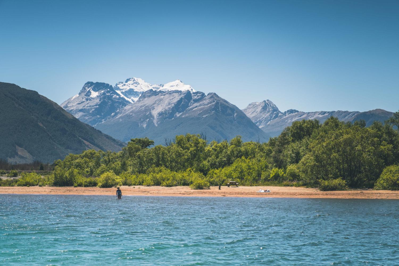 Badegast an einem Strand mit Bergen im Hintergrund