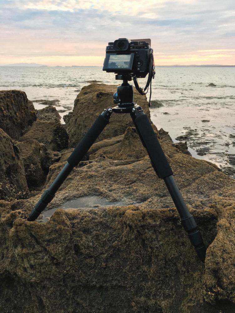 Fujifilm Kamera auf einem Feisol Stativ auf Steinen am Wasser
