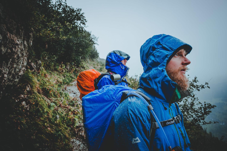 Zwei Perspnen stehen im Regen mit blauen Regenjacken