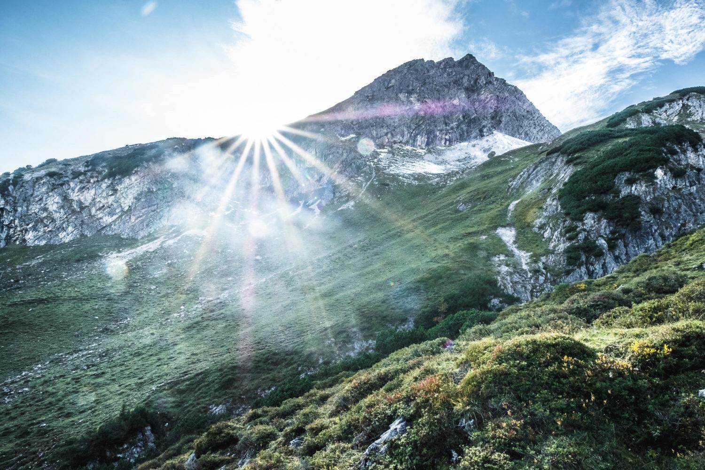 Sunstar am Berghang mit grünen WIesen