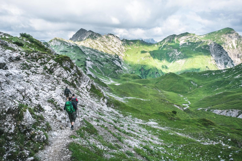Drei Wanderer auf einem felsigen Pfad im Gebirge