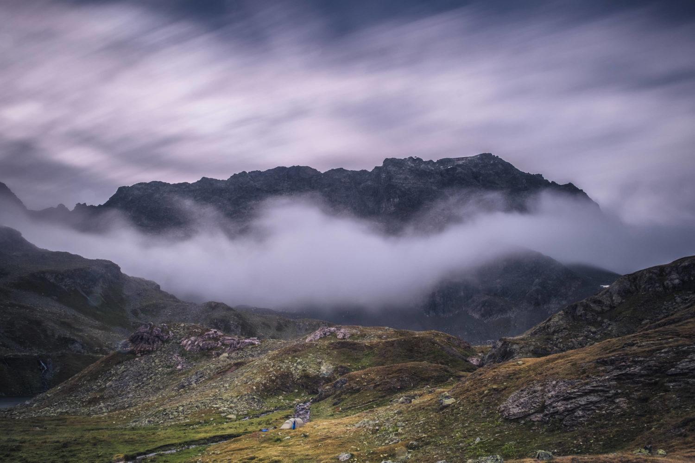 Langzeitbelichtung von Wolken vor einer Bergkulisse in Bivio in