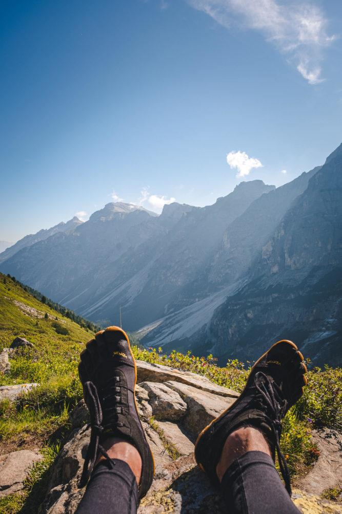Füße mit Zehenschuhen ragen ins Bild mit Bergen dahinter