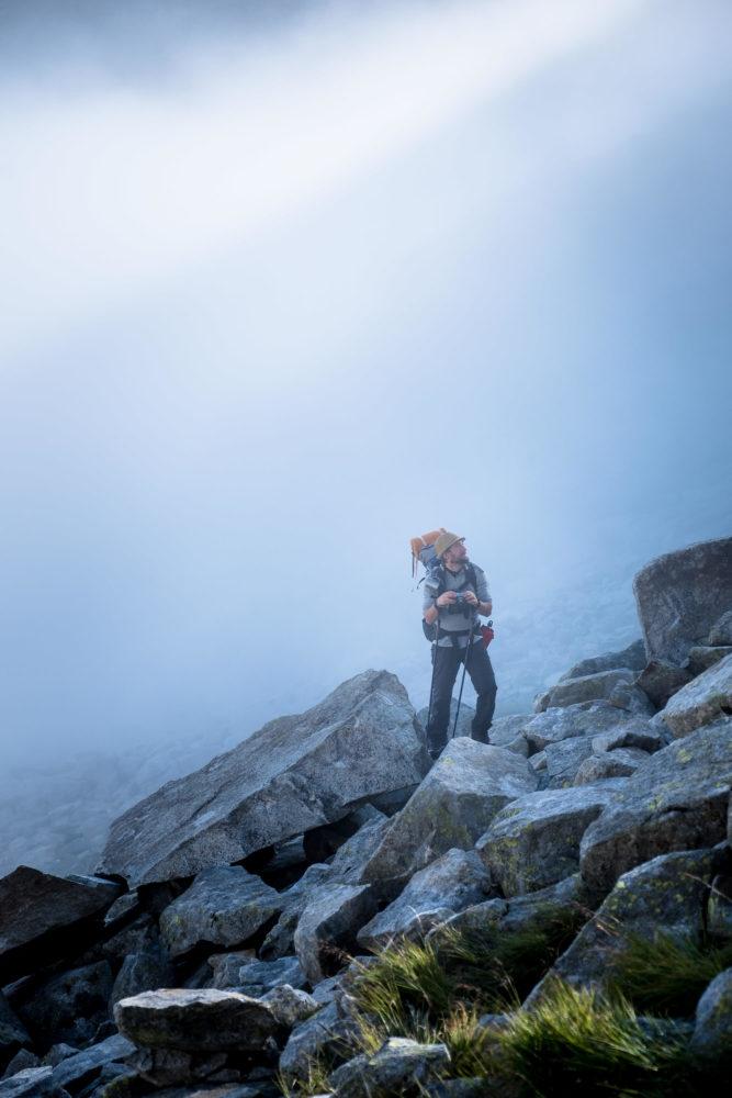 Wanderer steht in verblocktem Gelände