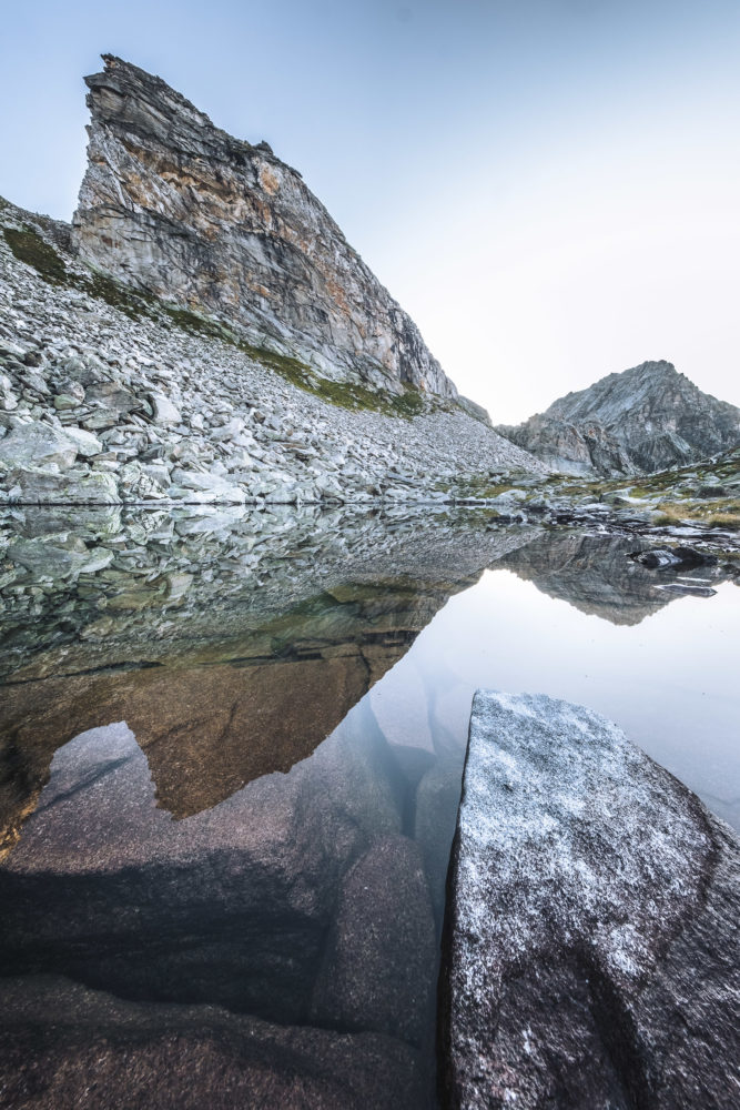 Spiegelung eines Bergs in einem Bergsee mit Gipfel im Hintergrund