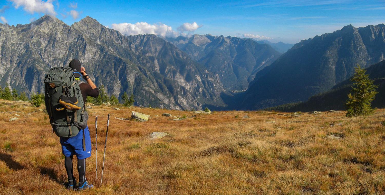 Fotograf mit großem Rucksack fotografiert Bergkette im Hintergrund