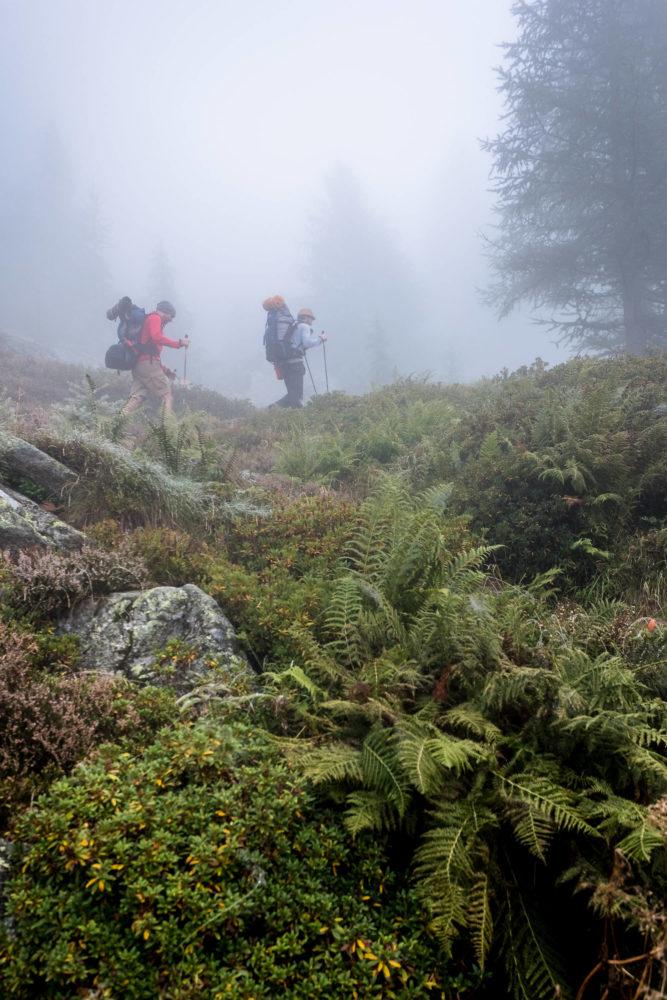 Zwei Wanderer laufen durch den Nebel im Val Bavona