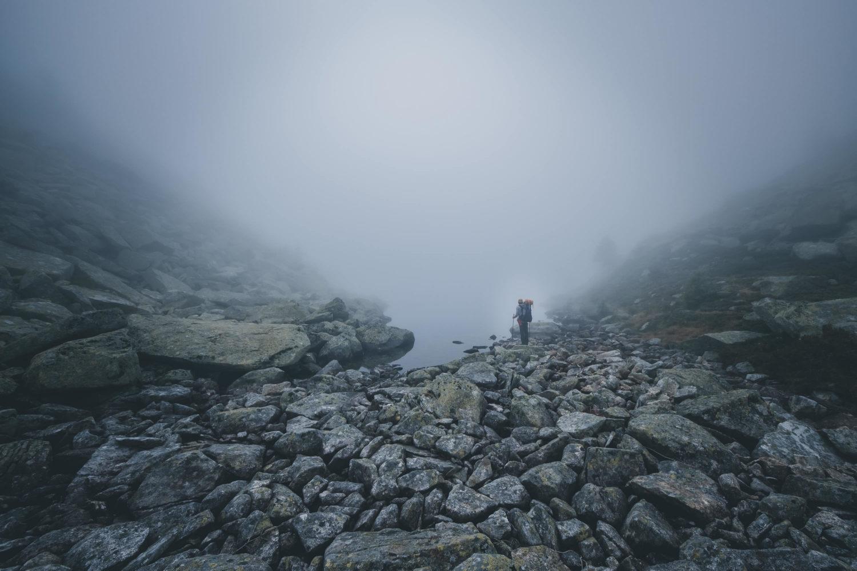 Wanderer steht zwischen Felsen an einem See