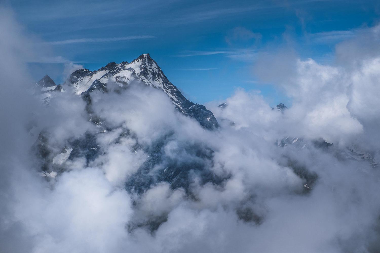 Berg mit schneebedeckten Hängen zwischen Wolken