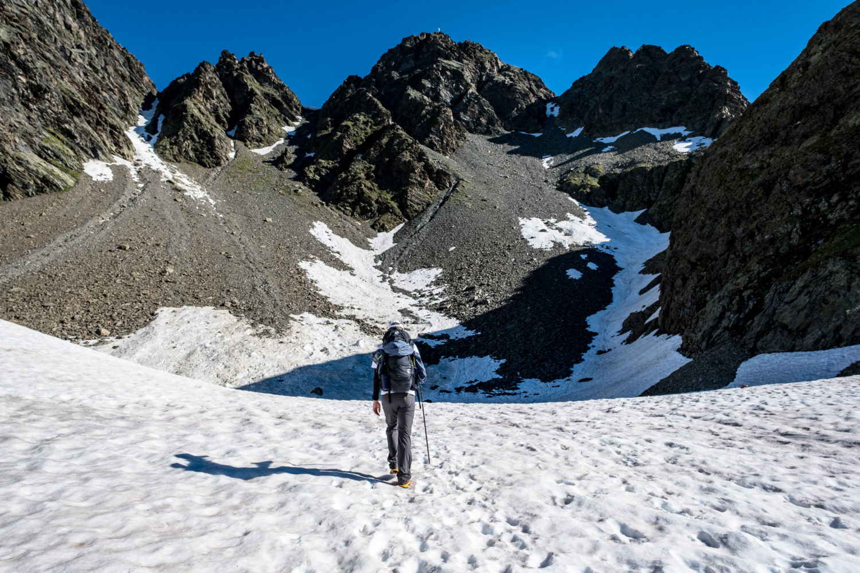 Wanderer läuft durch Schnee auf Berghänge zu