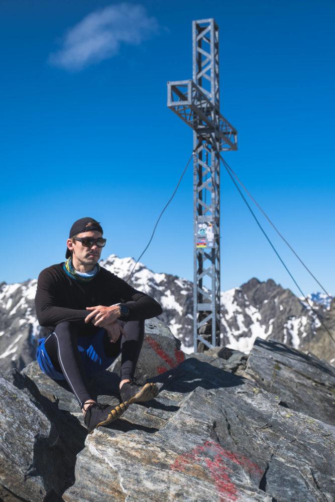 Jan Becker sitzt neben dem Gipfelkreuz des Zischgeles