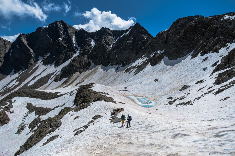 Zwei Wanderer laufen durch den Schnee in einem Bergkessel
