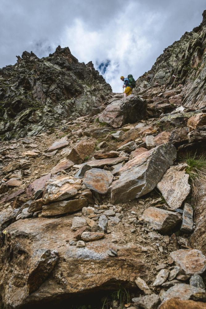 Wanderer steigt steilen Geröllhang ab