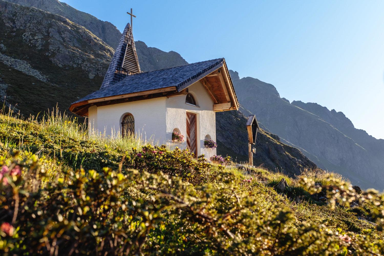 Kapelle im Morgenlicht zwischen Alpenrose auf der Sellrainer Hüttenrunde